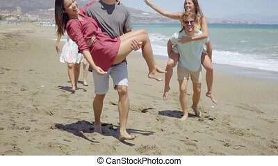 Friends carrying each other on beach