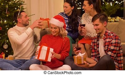 friends celebrating christmas and giving presents -...