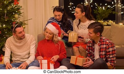 friends celebrating christmas and having presents -...
