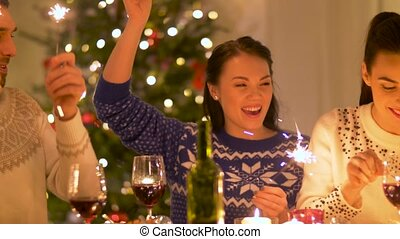friends celebrating christmas at home dinner party -...
