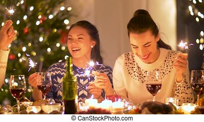 friends celebrating christmas at home dinner party