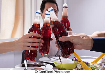 Friends Celebrating With Bottles Of Lemonade Drink