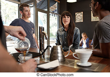 Friends chatting at counter in modern coffee shop