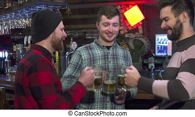 Friends clink their glasses at the pub