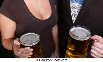 Friends clinking beer glasses against the background of the female breast