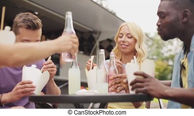 friends clinking bottles of drinks at food truck - leisure,...