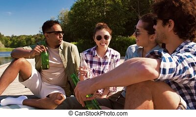 friends clinking drinks on wooden pier at lake - leisure, ...
