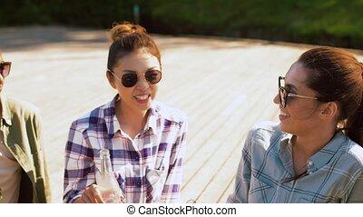 friends clinking drinks on wooden terrace - leisure, picnic...