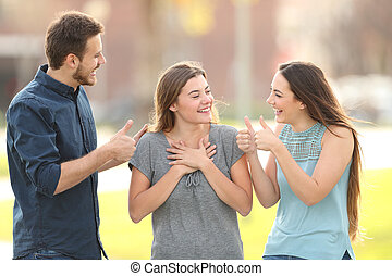 Friends congratulating a happy girl in the street