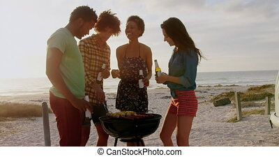 Front view of group of diverse friends cooking food on barbecue at beach. They are smiling and having fun 4k