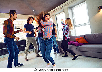 Friends dance at a student's party in the apartment.