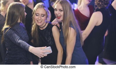 Friends dancing at a party, girls take selfie