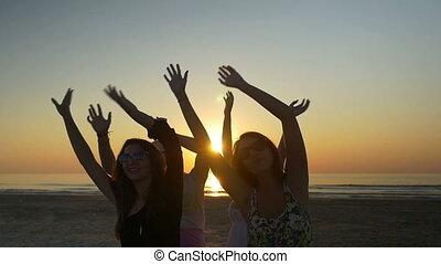 Friends dancing happily and waving their hands in the air at the beach at sunrise