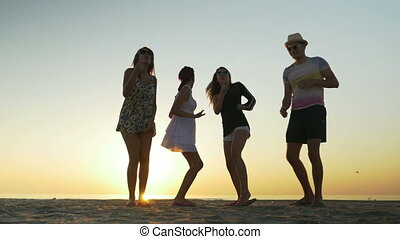 Friends dancing on the beach at sunrise