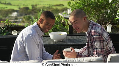 Friends discussing and using a smartphone on a rooftop - ...
