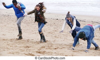 Friends Doing Handstands On A Winter Beach - A group of...