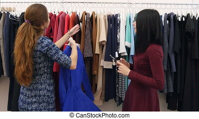 Friends doing shopping together in clothes boutique, taking photos using smartphone