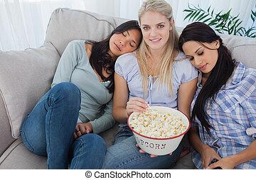 Friends dozing on blonde friends shoulders eating popcorn
