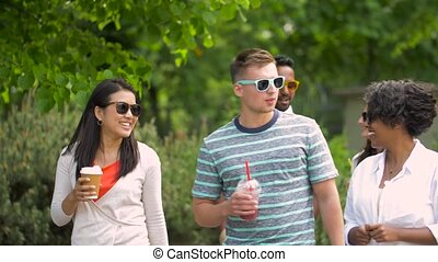 friends drinking coffee and juice walking in park - people,...