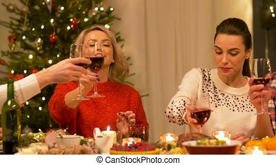 friends drinking wine at christmas dinner party - holidays...