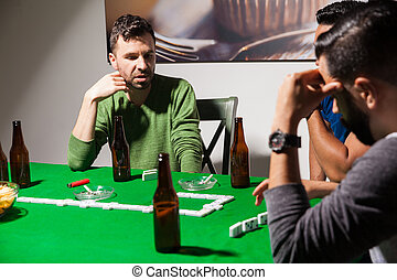 Friends during a dominoes game at night - Portrait of a ...