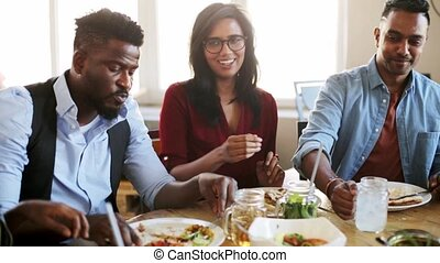 friends eating and clinking glasses at restaurant