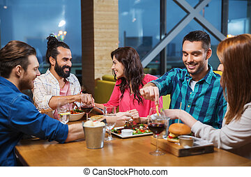 friends eating and tasting food at restaurant - leisure,...