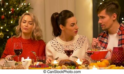 friends eating at home christmas dinner party - holidays and...