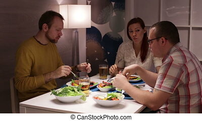 Friends eating at the table and talking