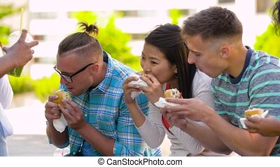 friends eating burgers or sandwiches in park - people, food...
