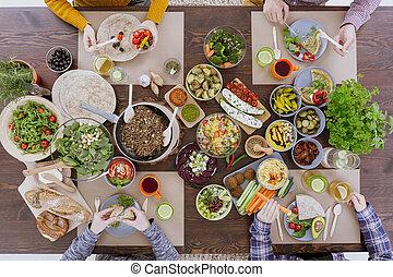 Friends eating healthy lunch - Friends sitting beside wooden...