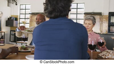 Friends eating pasta together - Front view of a multi-ethnic...
