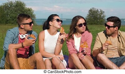 friends eating pizza at picnic in tallinn park - friendship,...