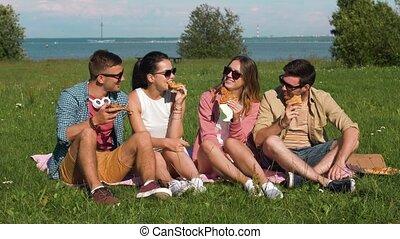 friends eating pizza at picnic in tallinn park - friendship,...