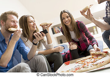 Friends eating pizza in th room - Group of young people ...