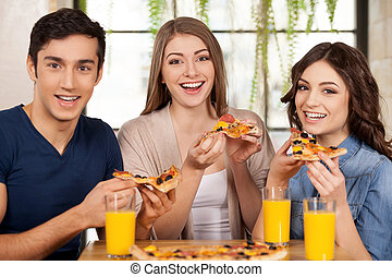 Friends eating pizza. Three cheerful young people eating pizza and smiling at camera while sitting together at the restaurant