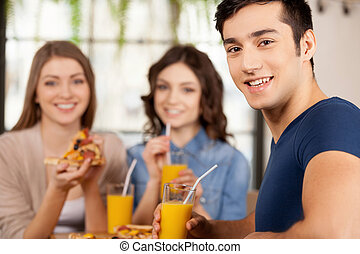 Friends eating pizza. Three cheerful young people eating pizza at the restaurant while man looking over shoulder and smiling at camera