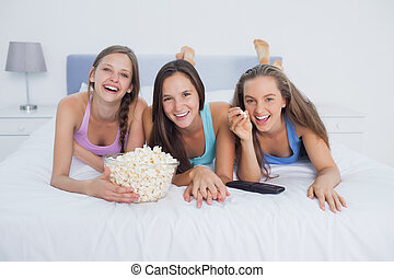Friends eating popcorn and watching tv