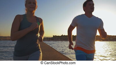 Steadicam shot of two friends having a morning jog. They are ending it with a jump and deep breath.