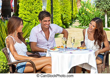 Friends enjoying a meal in a tropical garden