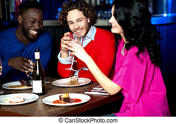 Friends enjoying dinner at restaurant