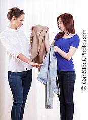 Friends exchanging jackets - Female friends during...