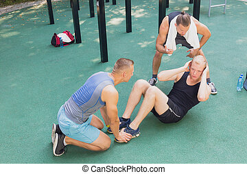 Friends exercising at outdoor gym