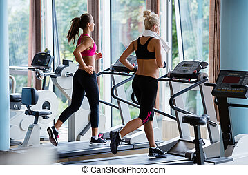friends exercising on a treadmill at the bright modern gym -...