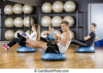 Friends Exercising With Medicine Ball In Gym