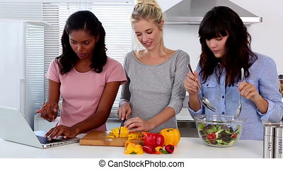 Friends following an online recipe then preparing a salad