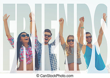 Friends forever. Low angle view of four cheerful young people holding hands and keeping arms raised while standing against sky