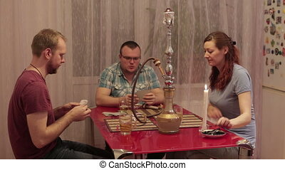 Friends fun with a hookah and playing cards