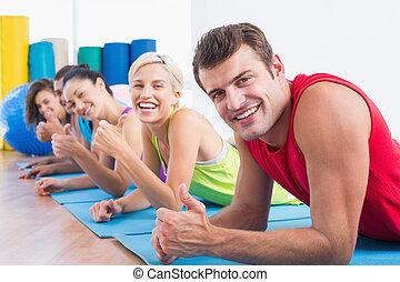friends, gesturing, daumen hoch, während, liegen, auf, matten, an, turnhalle