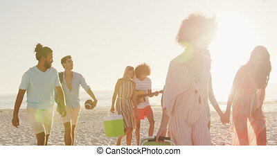 Friends going to party on beach - Side view of mixed race ...